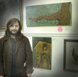 • the artist poses with his award-winning art on opening night.